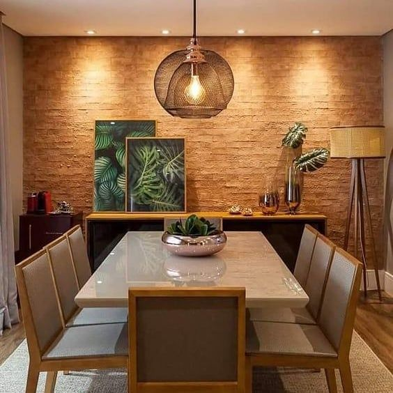 O revestimento traz a tonalidade do tijolo natural, combinado com os tons de madeira que trouxeram um aspecto de brasilidade à sala de jantar, pela escolha da luminária de palhinha e dos itens decorativos que lembram uma vegetação.