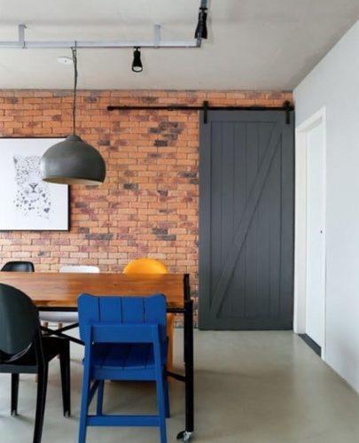 """Cozinha com mesa de madeira e pés em ferro, iluminação em trilho e porta de correr no estilo """"celeiro""""."""