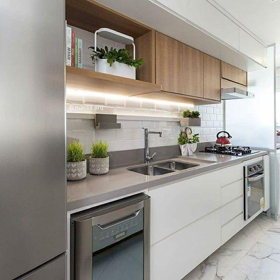 Cozinha pequena com marcenaria menos profunda. Parede com revestimento de metrô e piso com revestimento de mármore.