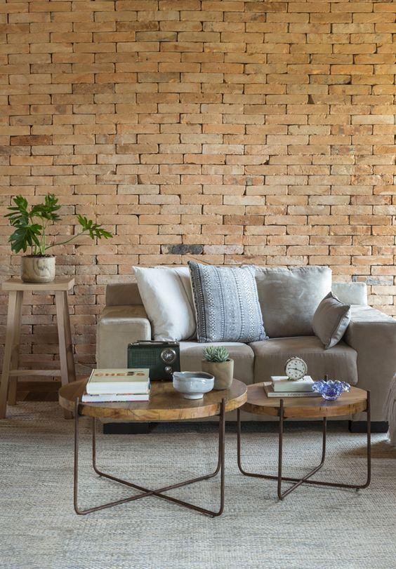 Parede de sala de estar com junta seca. Mesinhas redondas de centro, sofá e planta.