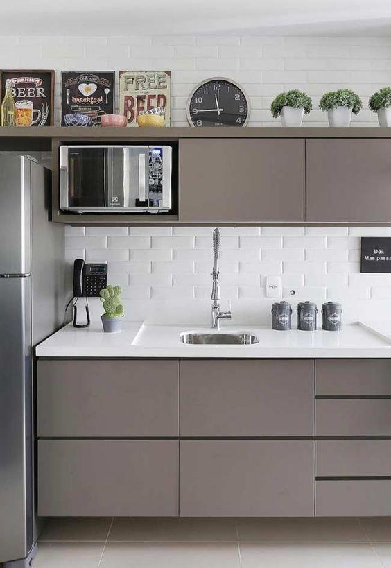 Cozinha brinca com a ideia de claro e escuro, com uma base branca e marcenaria escura com linhas retas.  Parede com revestimento metrô.