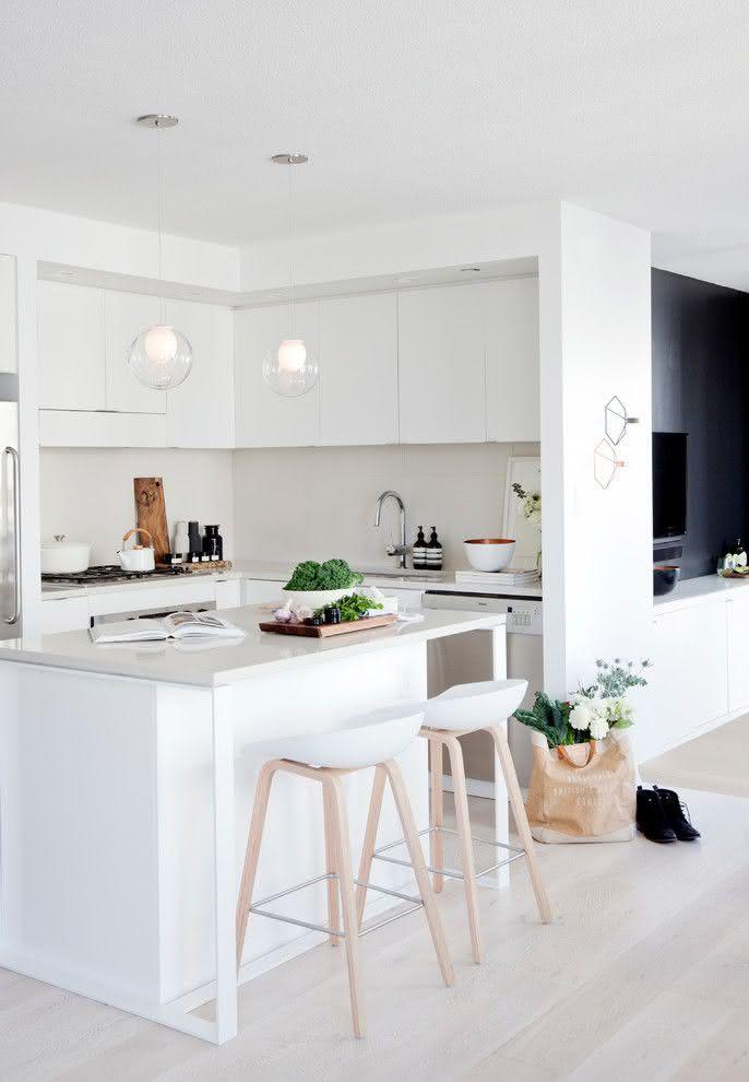 Cozinha de canto, toda em branco e com linhas simples para ampliar o espaço. Ilha central serve como apoio ao preparo de refeições e bancada de refeições rápidas.
