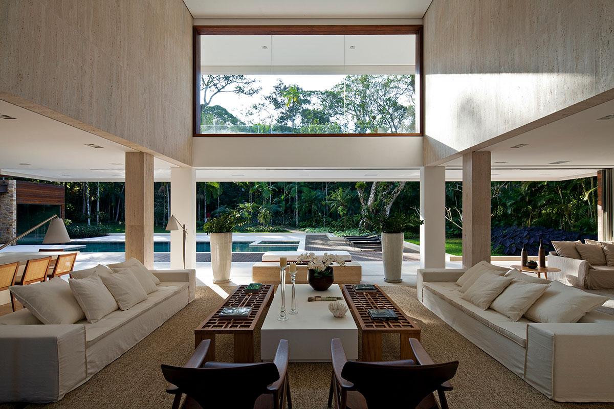 Sala de estar integrada com área externa. Iluminação natural e piso superior com parede de vidro. Estilo Contemporâneo