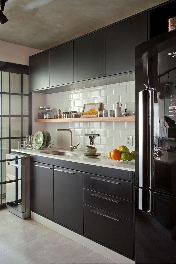 Cozinha pequena com decoração industrial; marcenaria preta, geladeira preta, teto revestido com cimento queimado, parede com revestimento do metrô e piso de porcelanato.