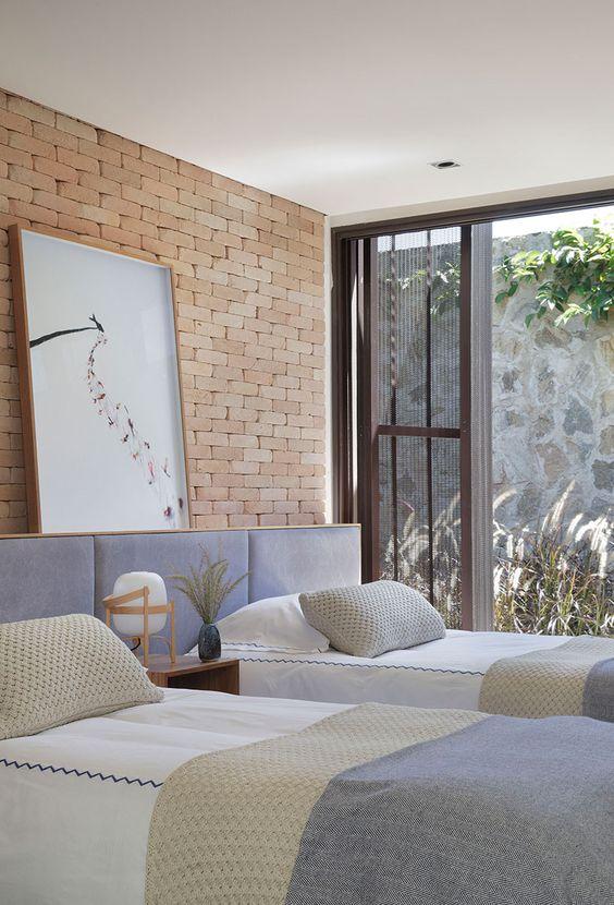 Quarto minimalista com iluinação natural e acesso a área externa.