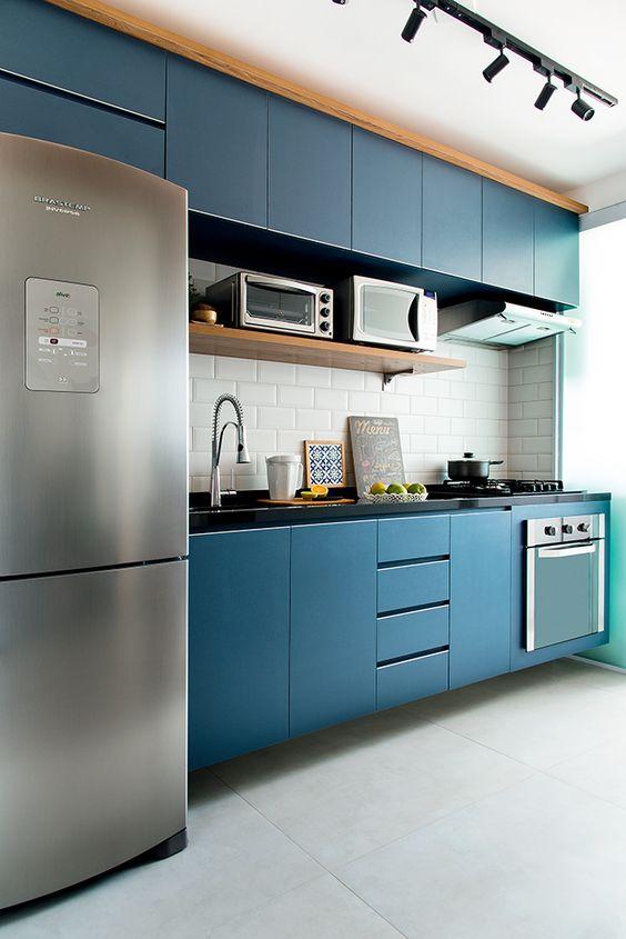 Cozinha pequena com marcenaria azul, parede com revestimento do metrô na cor branco. E trilho com sposts de luz.