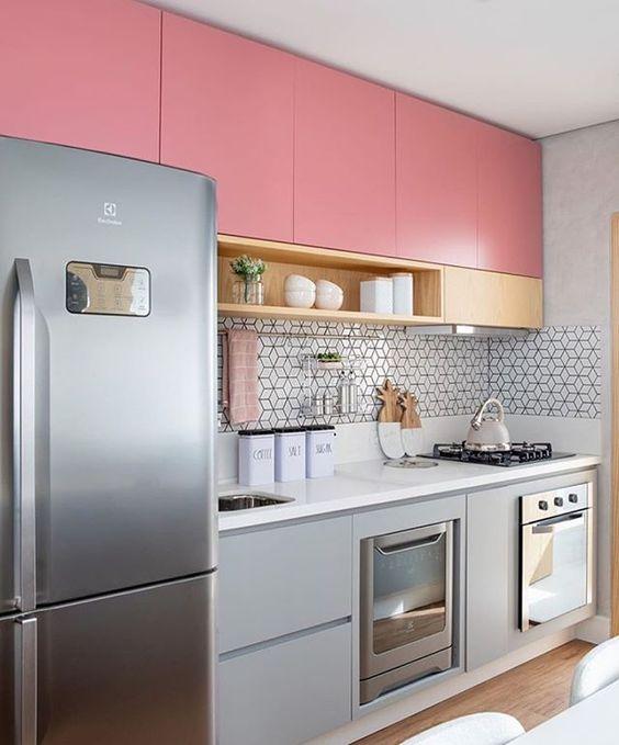 Cozinha com vários elementos combinados de maneira harmoniosa. Armário com cor rosa e madeira clara, e parede com revestimento geométrico.