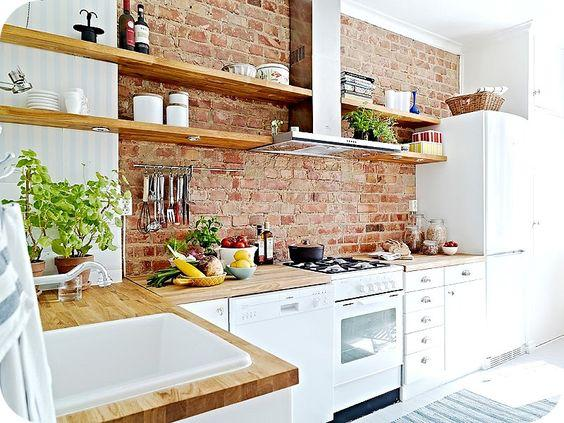 Com aspecto bem rústico, o tijolo é o ponto central do projeto da cozinha, que traz poucos armários.