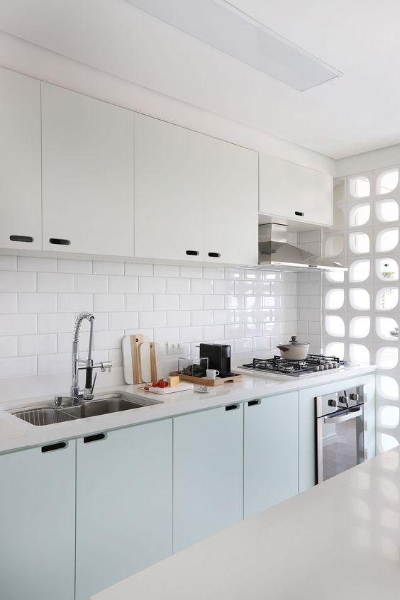 Cozinha pequena branca com um leve toque de verde menta nos armários baixos. Parede com revestimento de metrô e cobogó como divisória entre cozinha e lavanderia.