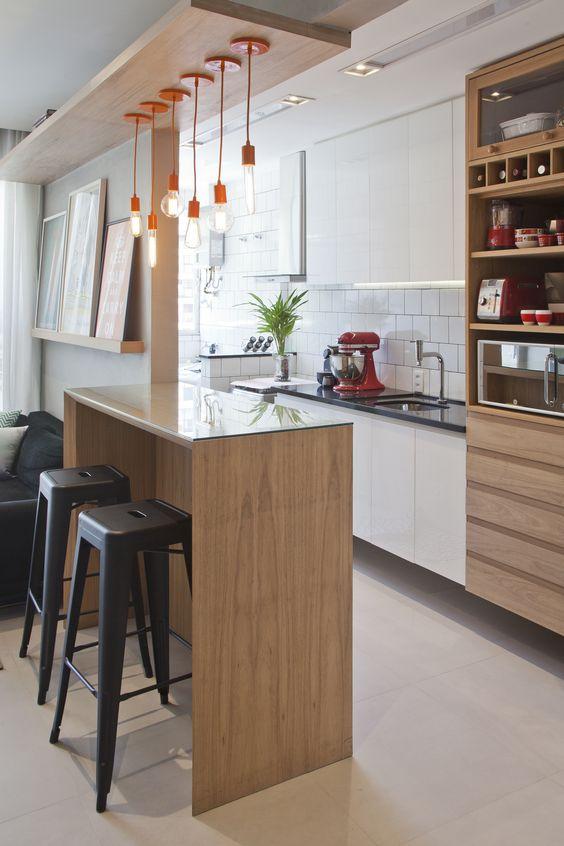 Cozinha pequena integrada com sala de estar através de uma bancada de madeira.