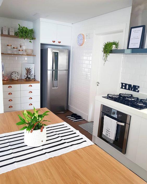 Com estilo escandinavo, cozinha apresenta vários elementos em alta no décor: madeiras claras, tons de cobre e azulejo de metrô.