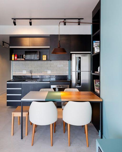 Cozinha moderna com marcenaria preta, tijolo aparente e toques de cor no mobiliário.