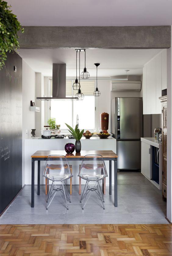 Cozinha pequena com decoração industrial. bancada central que abriga cooktop e coifa, piso de madeira com paginação escama de peixe.