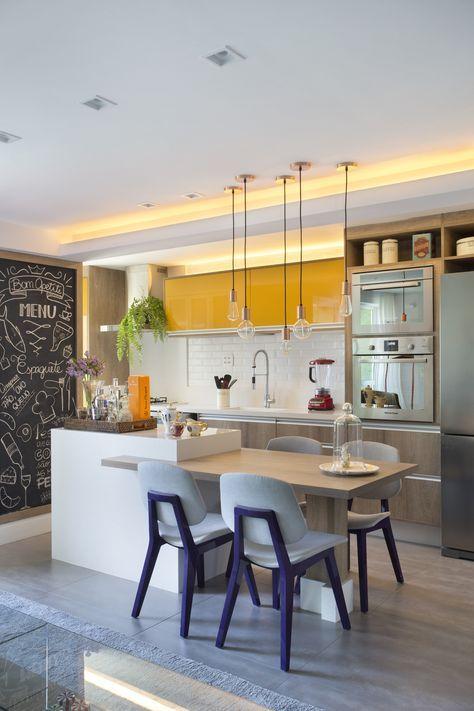 Cozinha com bancada de refeição integrada a uma área de apoio no preparo dos alimentos.  Armários de madeira que vão do piso ao teto e um toque de amarelo nos armários de cima.