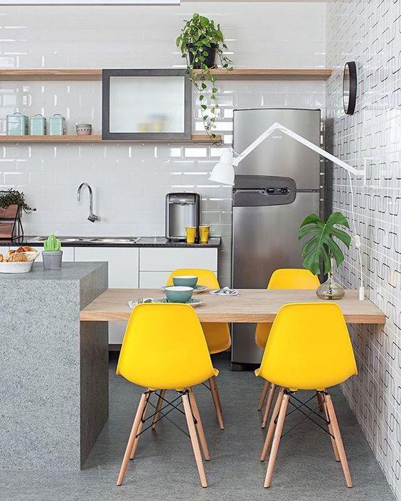 Cozinha com revestimento do metrô na parede do fundo e revestimento geométrico na parede lateral. Cadeiras amarelas com pés de palito