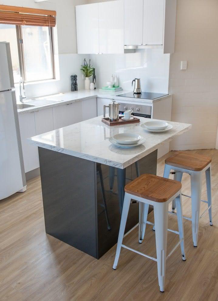 Cozinha minúscula traz eletrodomésticos pequenos com ilha central que de um lado serve como espaço extra de armazenamento, do outro para refeições. Cozinha branca com piso de madeira.