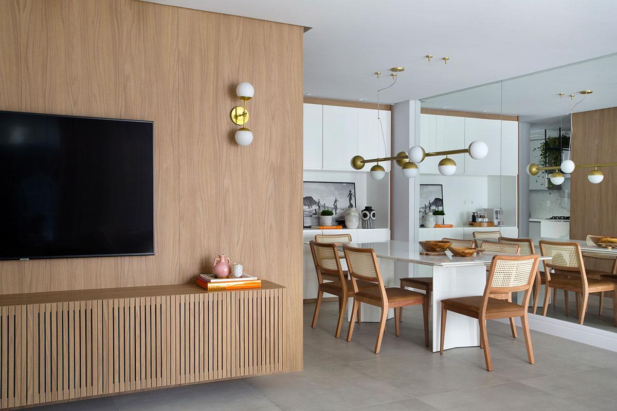 Sala de jantar com espelhos na parede, luminária de teto e mesa. Sala de estar com painel de madeira clara na parede e um armário.