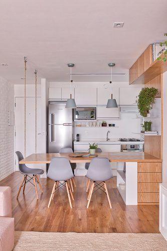 Cozinha com decoração escandinava. Armários e mesa de madeira.