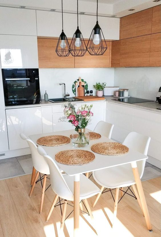Cozinha com decoração escandinava, armários na cor madeira clara e branco, além de uma mesa pequena no centro da cozinha.