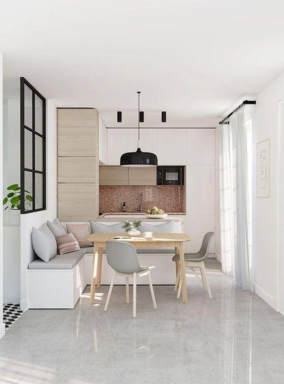 Cozinha escandinava com tons claros e integrada a sala de jantar. Sofá de canto com tom pastel e mesa de madeira. Na lateral tem uma entrada de luz natural.