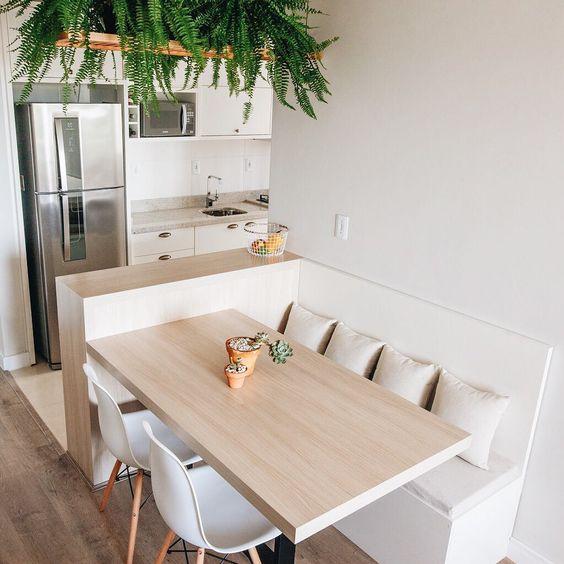 Cozinha integrada com sala de jantar. Mesa conectada com ilha e plantas suspensas.