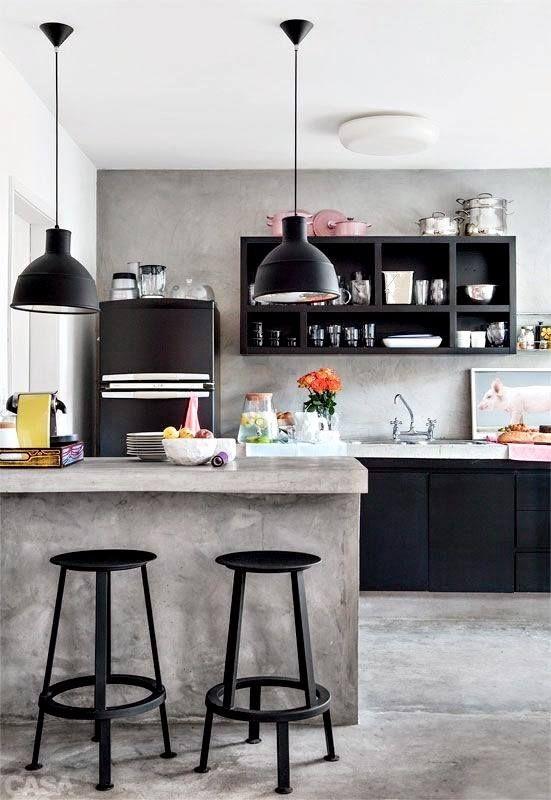 Cozinha com tons sóbrios. Revestimento de cimento queimado  no piso, bancada e parede. Armários, luminárias, eletrodomésticos e bancos, todos na cor preto.
