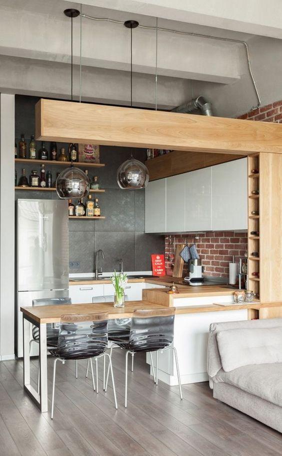 Cozinha pequena com estilo industrial. Revestimento de tijolinhos aparentes, instalações aparentes, teto de cimento queimado, piso de madeira cinza e armários e mesa de madeira clara.