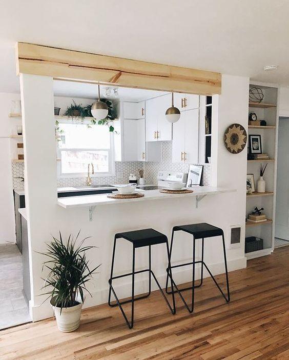 Cozinha escandinava integrada com sala através do balcão. Piso de madeira cinza e marrom. Armários brancos.