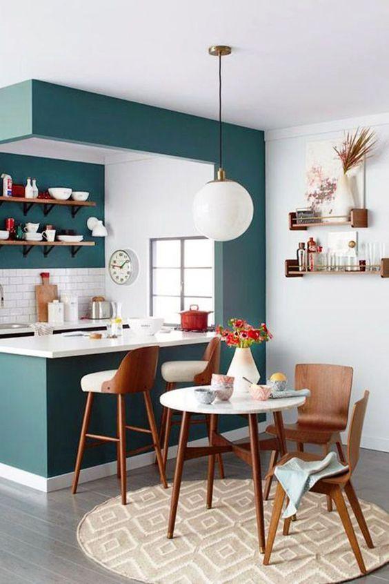Cozinha e sala de jantar integradas por uma ilha. Ambiente branco com um toque de azul. Piso de madeira e revestimento do metrô branco.
