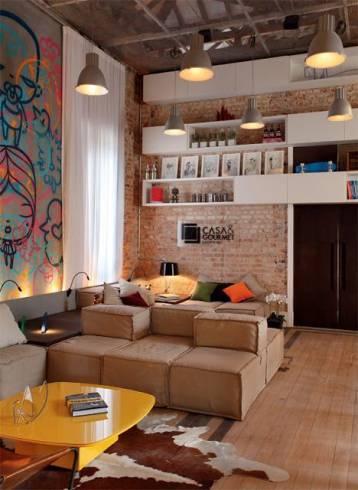 Aqui o revestimento é peça essencial no décor bem urbano e cosmopolita. Ambiente com pé direito duplo.