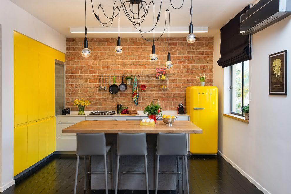Cozinha com elementos industriais e um toque de amarelo. Tijolinhos na parede do fundo e luminária de teto.