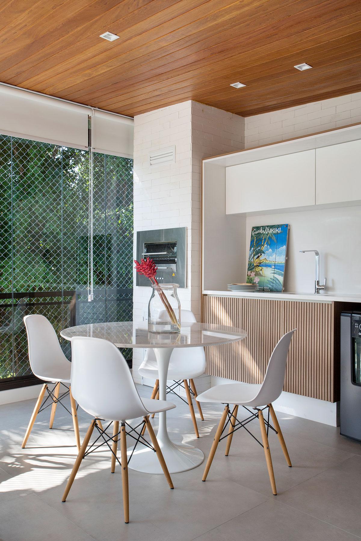 Cozinha clean com entrada de luz natural. Cadeiras brancas com pés de madeira e mesa redonda. Armários da pia com madeira ripada e teto de madeira.
