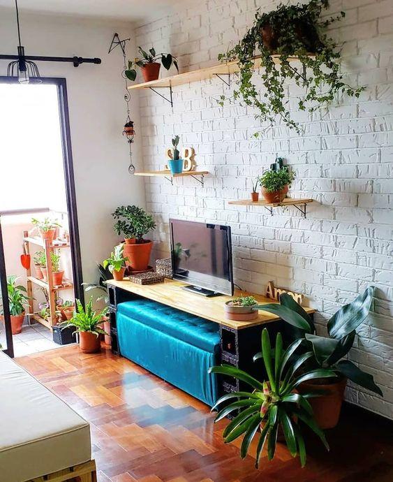 Nesta sala parece que a área externa invadiu a casa, repleta de plantinhas.  49 ideias de ambientes com tijolinho aparente
