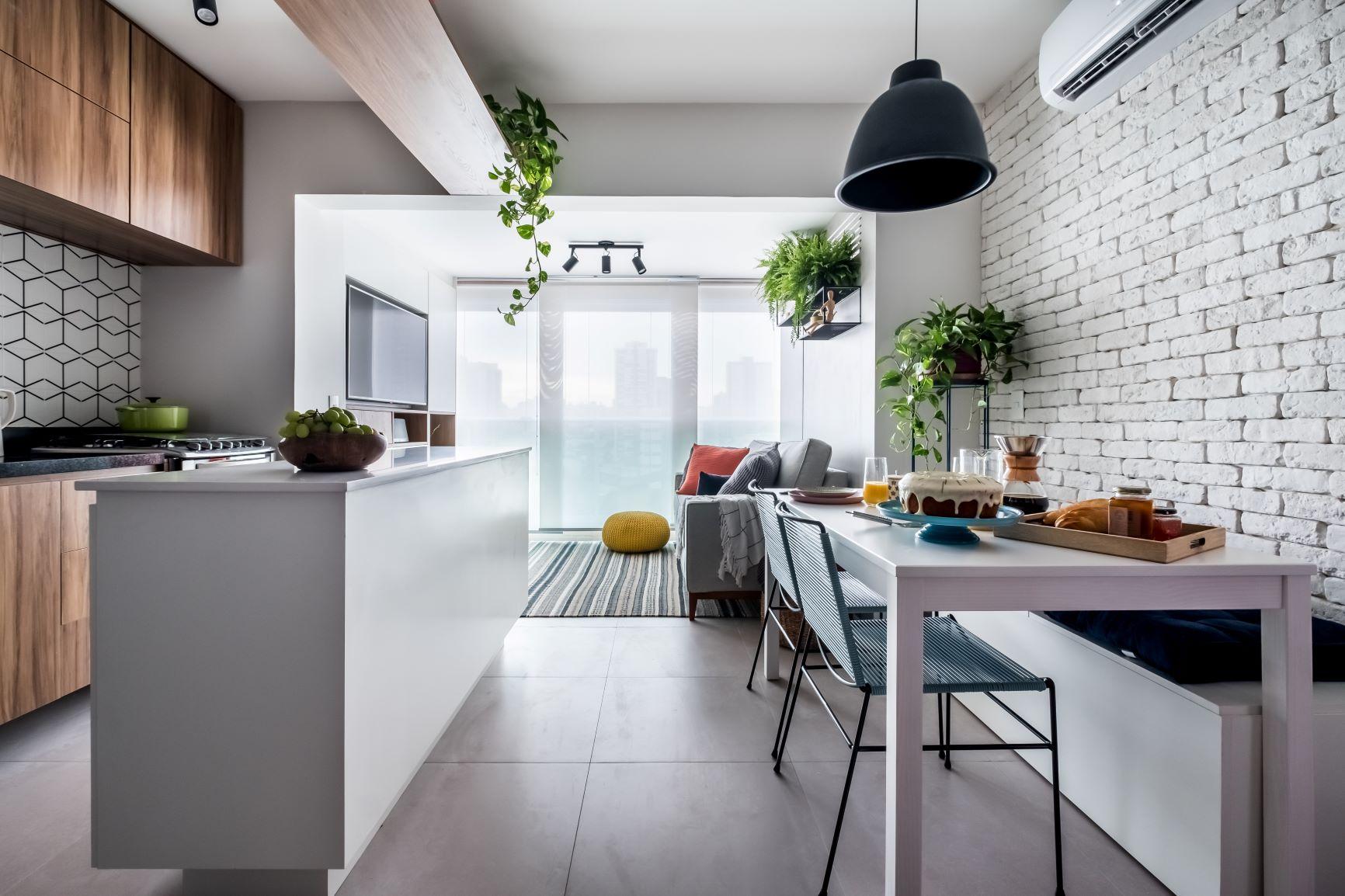 Apartamento com cozinha, sala de jantar e estar integrados. Uma ilha central na cozinha. Paredes revestidas com tijolinhos aparentes, cimento queimado e azulejos geométricos. Além de plantas na decoração.