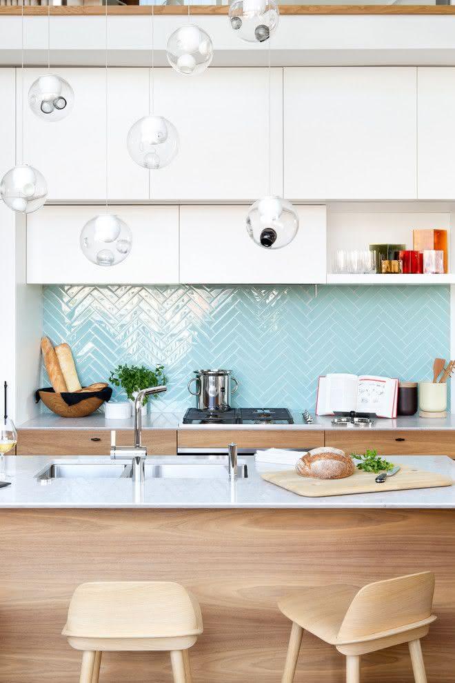 Cozinha com linhas retas, base em branco e madeira. Revestimento azul com paginação espinha de peixe.