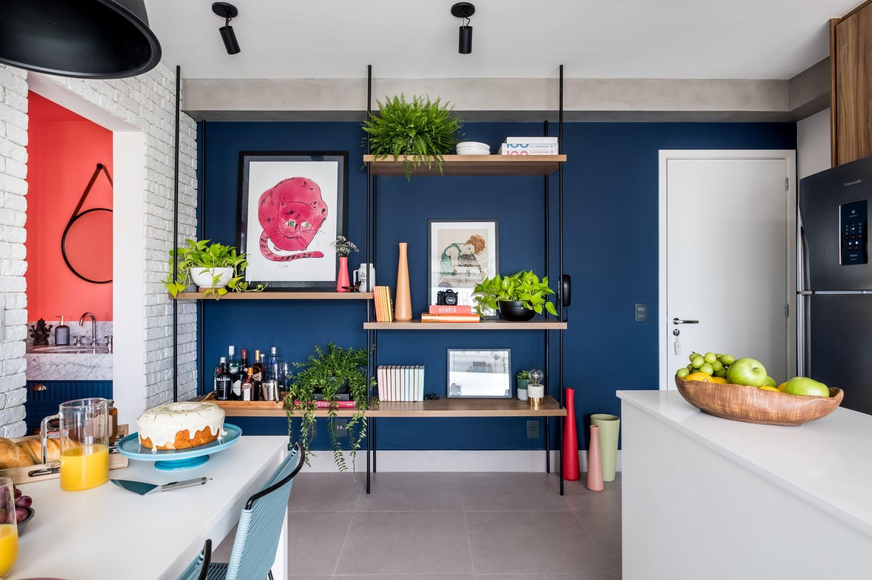 Apartamento com decoração moderna. Parede do fundo com pintura azul, prateleira com plantas e piso de porcelanato.