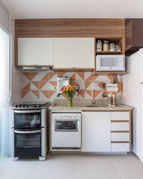 Cozinha com marcenaria de linhas retas do chão ao teto, com eletrodomésticos embutidos. E na parede revestimento geométrico.