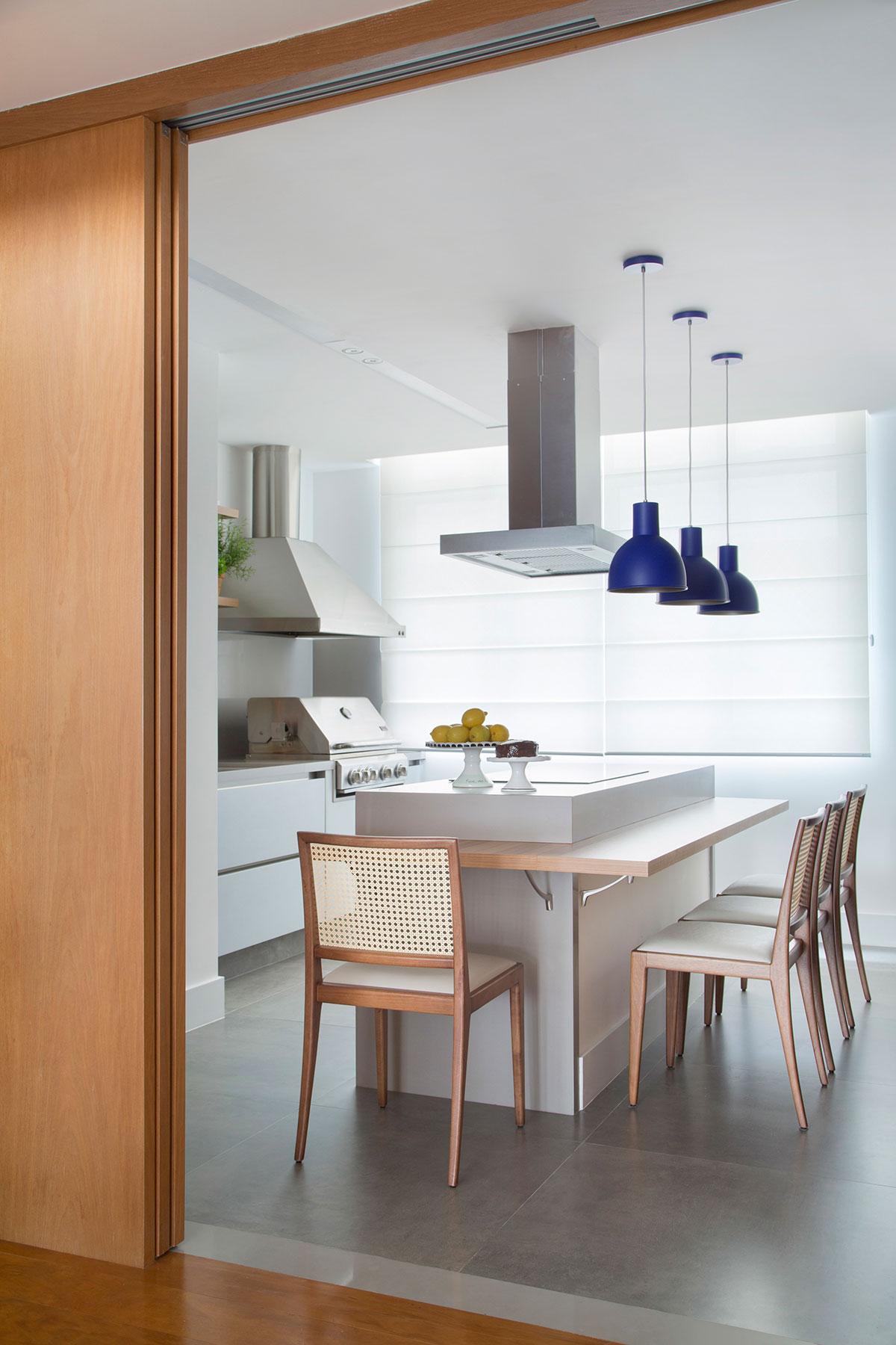 Cozinha com estilo contemporâneo, ilha central com balcão para refeições. Luminárias azuis de teto, depurador de ar e cadeiras de madeira.