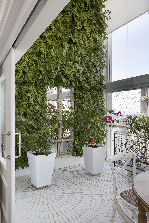 Varanda de pé direito duplo, com piso cerâmico, jardim vertical, vasos de plantas e mesa com cadeiras.