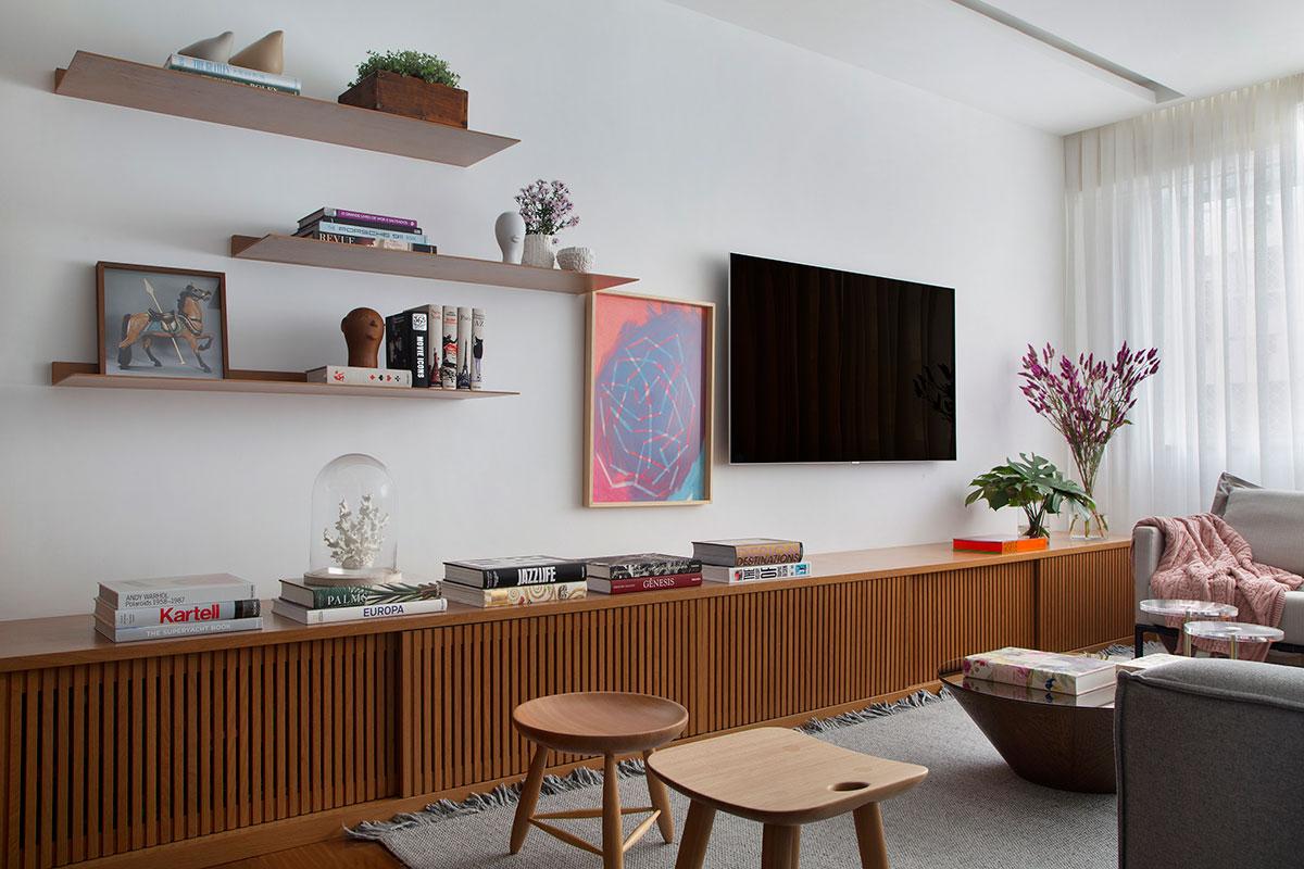 Sala de estar com armário baixo de madeira. E pintura branca na parede e teto. Prateleiras na parede.