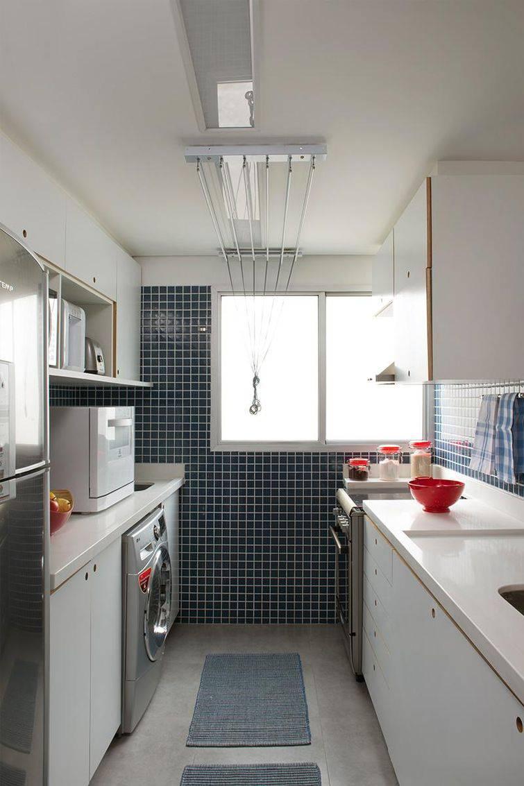 Cozinha e lavanderia integradas pela marcenaria e bancadas. Armários sem puxadores.