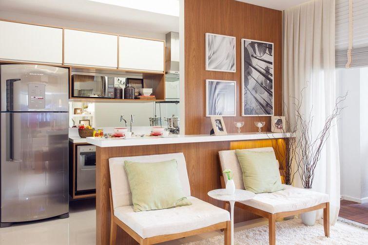 A cozinha americana apresenta uma bancada estreita. Parede com revestimento de madeira.