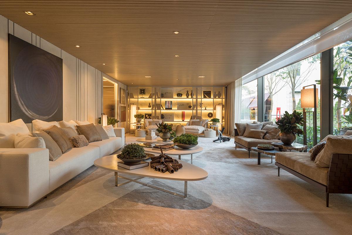 Living com teto de madeira ripada, sofás de tamanho grande, mesas de centro em formatos ovais, tapete que se estende por toda a sala e luz natural.