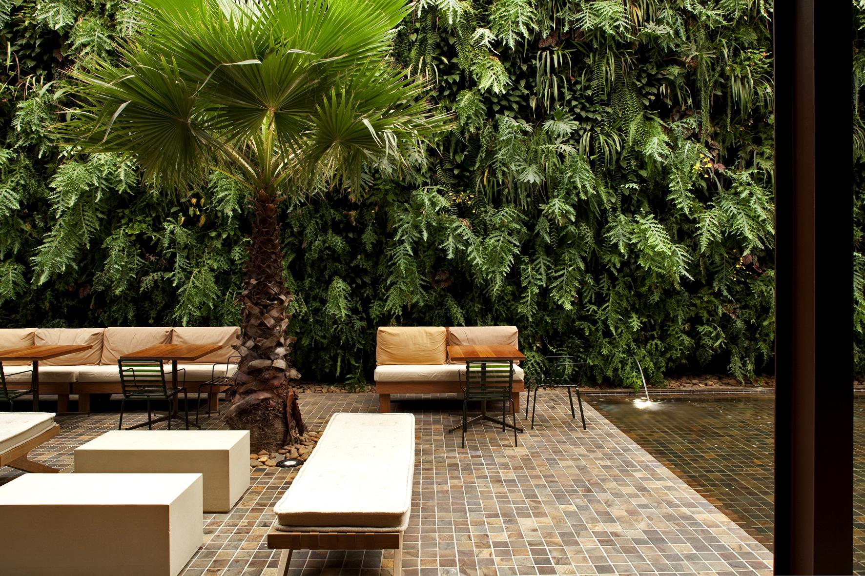 área externa com revestimento de pedra natural no piso, um exuberante jardim vertical e alguns bancos e sofás.