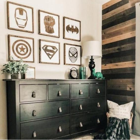 Ambiente com decoração de Super Heróis. Armário preto e parede com revestimento de madeira.