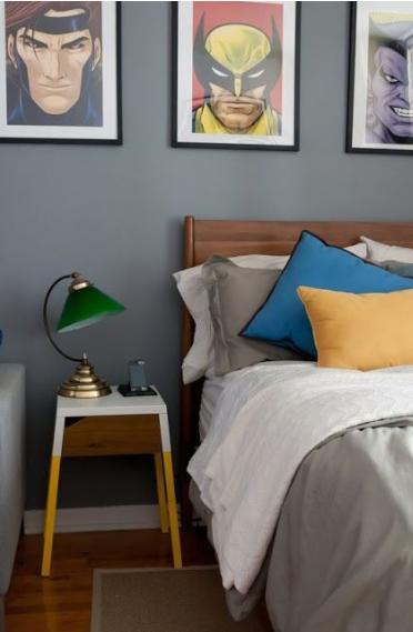 Quadros de Super-heróis, parede com pintura cinza, cama, luminária, criado mudo com pés de palito e piso com revestimento de madeira.