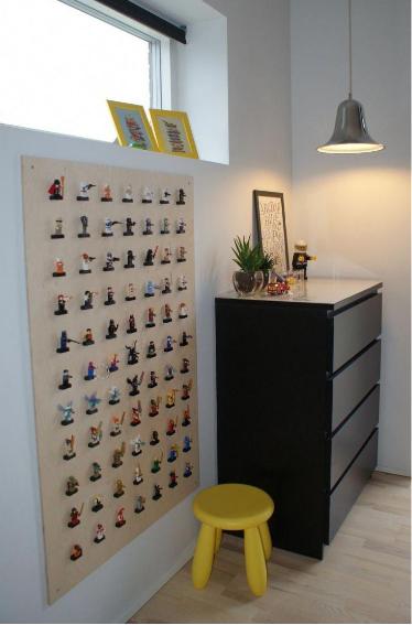 Ambiente com coleção de miniaturas na parede, armário preto, luminária de teto, banquinho amarelo e piso de madeira.