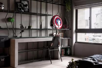 Apartamento com decoração de Super-Heroes. Escrivaninha de madeira e prateleira metálica de cor preta, plantas e parede com pintura de cimento queimado.