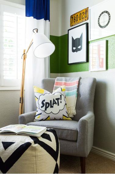 Apartamento com decoração de Super-Heróis, poltrona cinza, luminária de chão e quadros na parede.