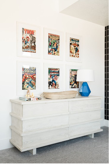 Ambiente com decoração de Super-Heróis, aparador branco, quadros de super-heróis e parede com pintura branca.
